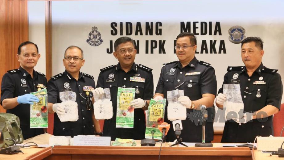 Mat Kasim (tengah) menunjukkan bungkusan dadah yang dirampas polis pada sidang media di IPK Melaka. FOTO Rasul Azli Samad