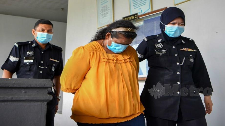 Suryaakala diiringi anggota polis selepas didakwa memperdagangkan manusia di Mahkamah Sesyen Ayer Keroh hari ini. Foto Amir Mamat