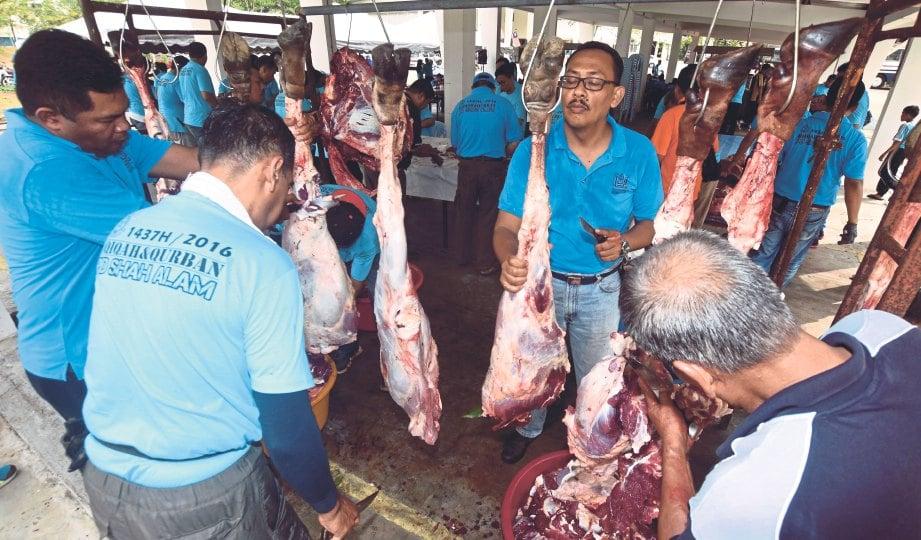 ANGGOTA polis bergotong-royong melapah dan memotong daging lembu korban pada majlis Ibadah Korban dan Akikah Ibu Pejabat Polis Daerah (IPD) Shah Alam, tahun lalu. - Gambar hiasan