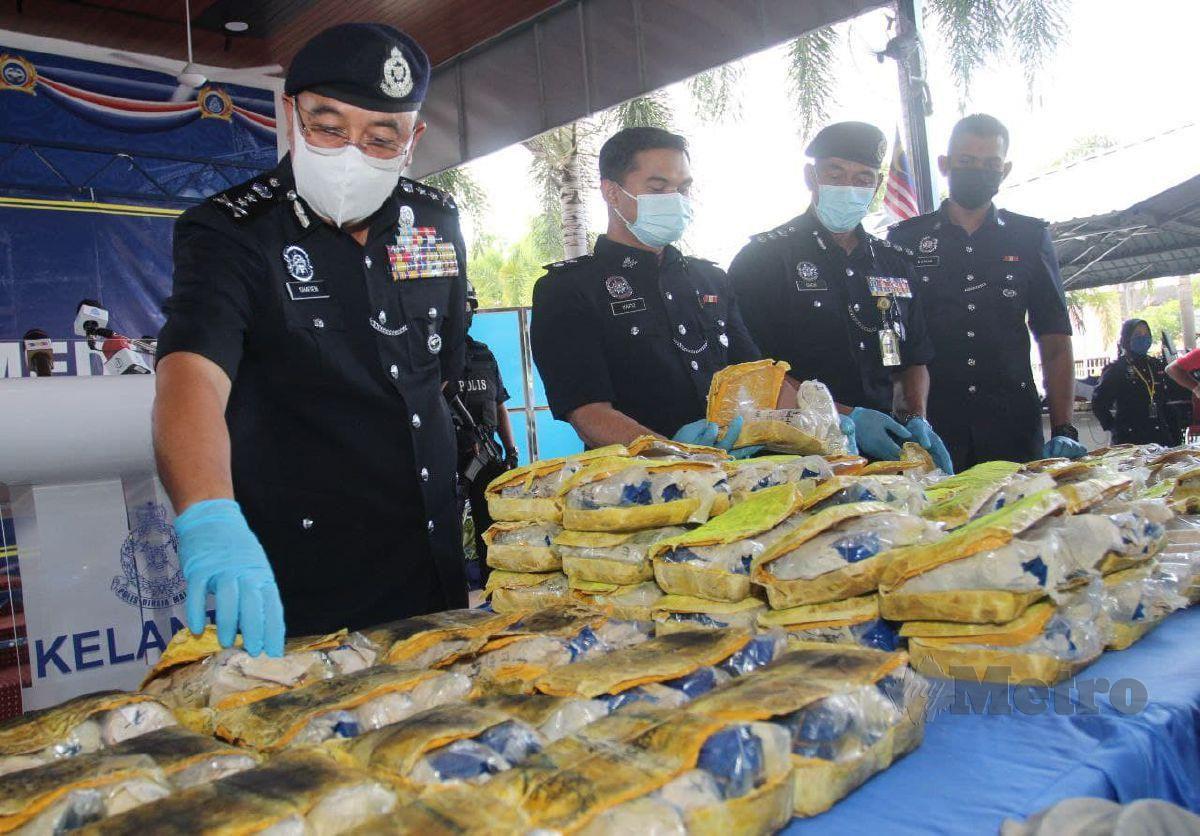 SHAFIEN (kiri) menunjukkan dadah yang dirampas. FOTO Nik Abdullah Nik Omar