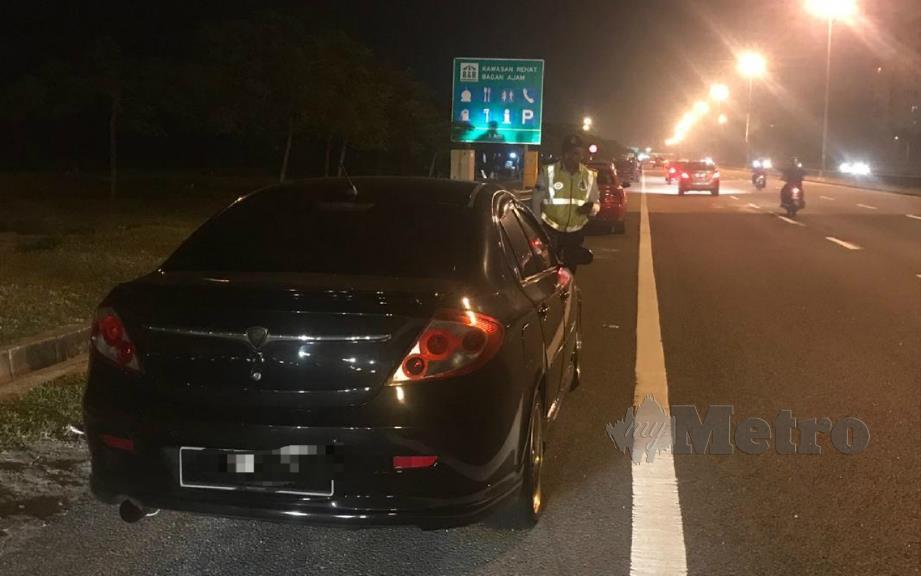 ANGGOTA trafik IPD SPU mengeluarkan saman pada pemilik kereta yang meletakkan kenderaan di lorong kecemasan di Lebuhraya Lingkaran Luar Butterworth (BORR). FOTO ihsan polis.