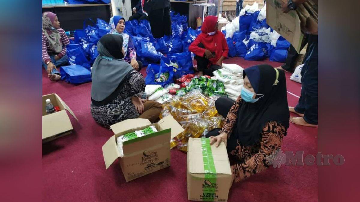 PETUGAS memasukkan barang bantuan ke dalam kotak sebelum diagihkan. FOTO Mohd Rashidi Yusuf