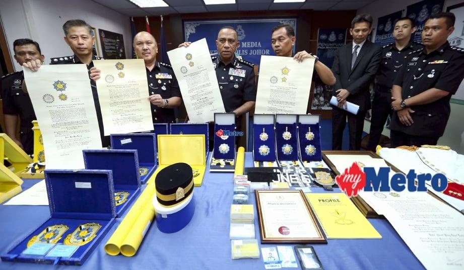 Mohd Khalil (tengah) menunjukkan sijil, pingat dan pelbagai barang rampasan polis Johor yang membongkar sindiket penawaran Darjah Kebesaran Negeri palsu. FOTO Mohd Azren Jamaludin