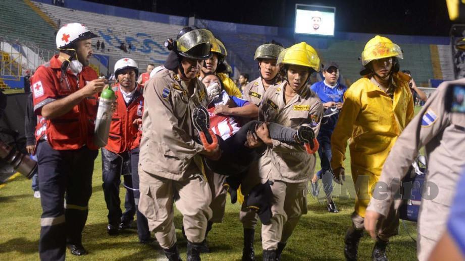 Anggota bomba mengusung wanita terbabit dalam pergaduhan penyokong bolasepak di Honduras. FOTO REUTERS