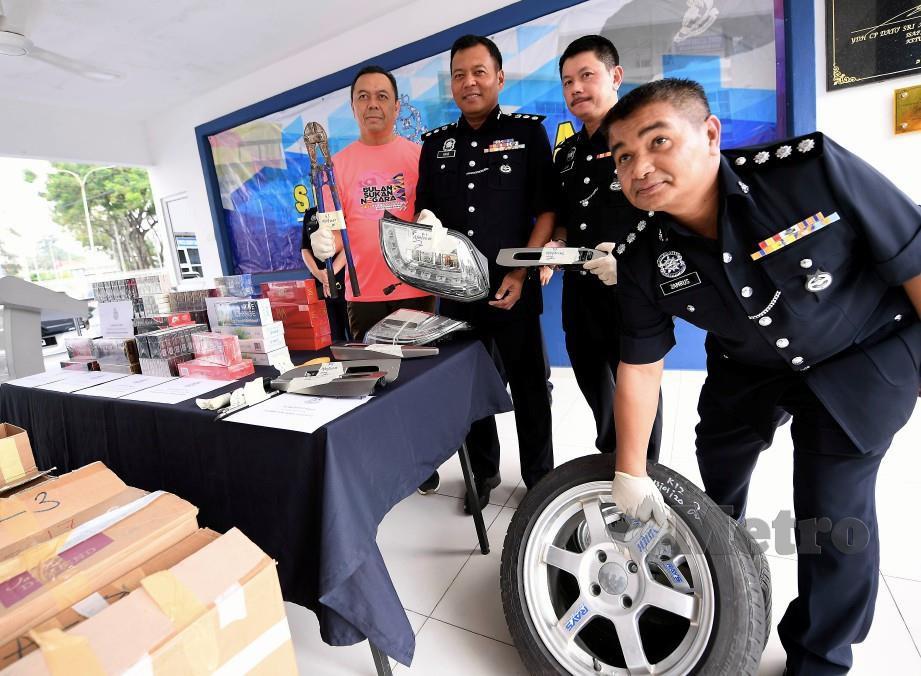 SHAMSUL Amar (tiga dari kanan) menunjukkan komponen kereta yang dicuri di kawasan tempat letak kereta sebuah pasar raya  di Bandar Bukit Tinggi Klang. FOTO BERNAMA