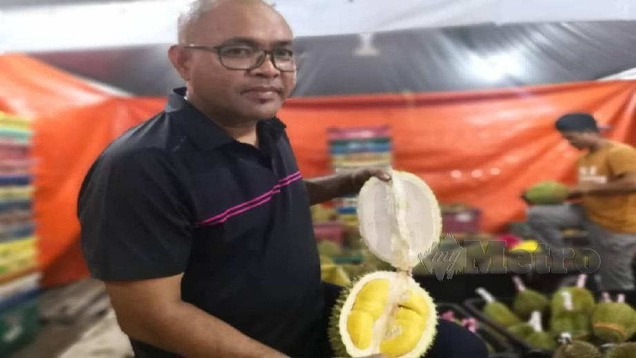 MOHAMAD Faizal menunjukkan durian Musang King yang dijual di Tapak Bazar Raya Pekan Tanjong Karang. FOTO Ihsan Pembaca.