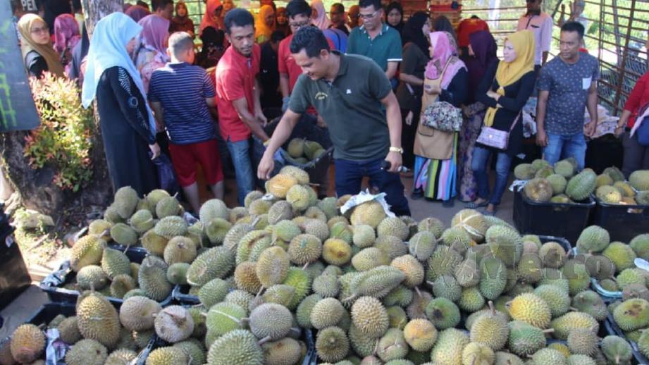 Orang ramai menyerbu durian yang dijual RM10 untuk satu beg plastik. FOTO Nik Abdullah Nik Omar