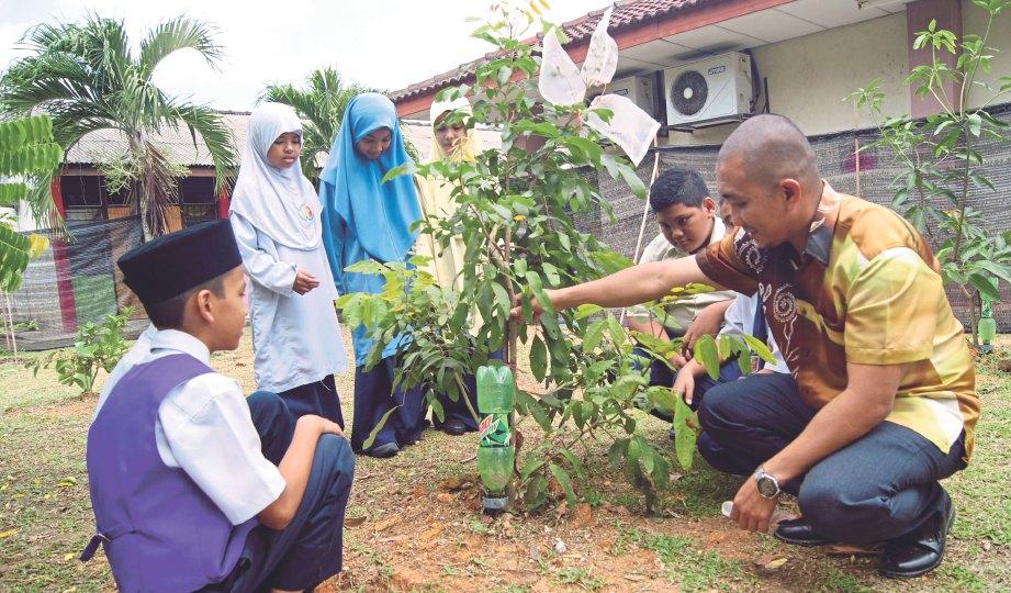 REDZUAN memberikan taklimat kepada murid mengenai pokok yang ditanam di tapak projek dusun sekolah.