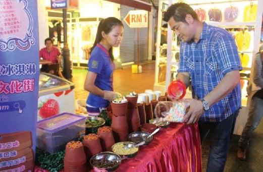 JASMINE bersama pak ciknya, The Chee Ker, 36 yang selalu membantu dia berniaga di Jonker Walk, Melaka.