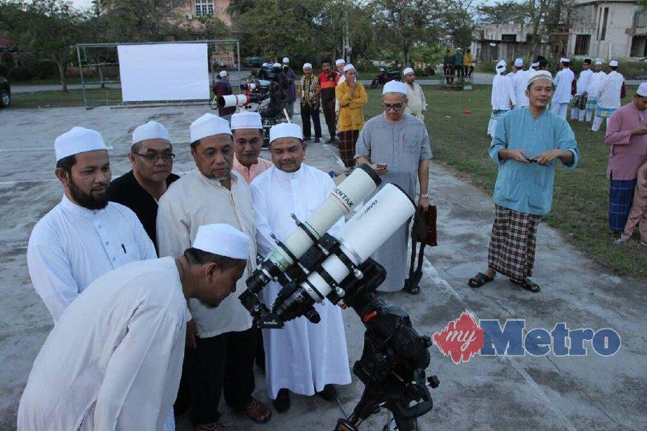Wan Muhammad Ezani (kiri) melihat kombinasi serentak tiga fenomena bulan, super moon, bulan biru, gerhana bulan, sekali dalam 265 tahun bersama dengan jemaah di pekarangan Masjid Putera Taman SBJ, Pasir Pekan. FOTO NIK ABDULLAH NIK OMAR