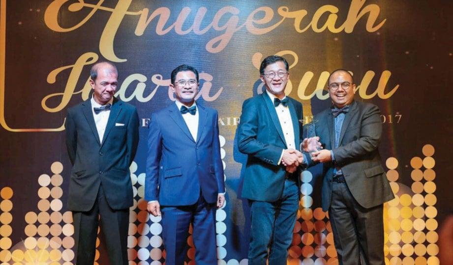 MURTADZA menerima anugerah disampaikan Ketua Pegawai Eksekutif The Holstein Milk Company Loi Tuan Ee sambil diperhatikan Azmi (dua dari kiri)
