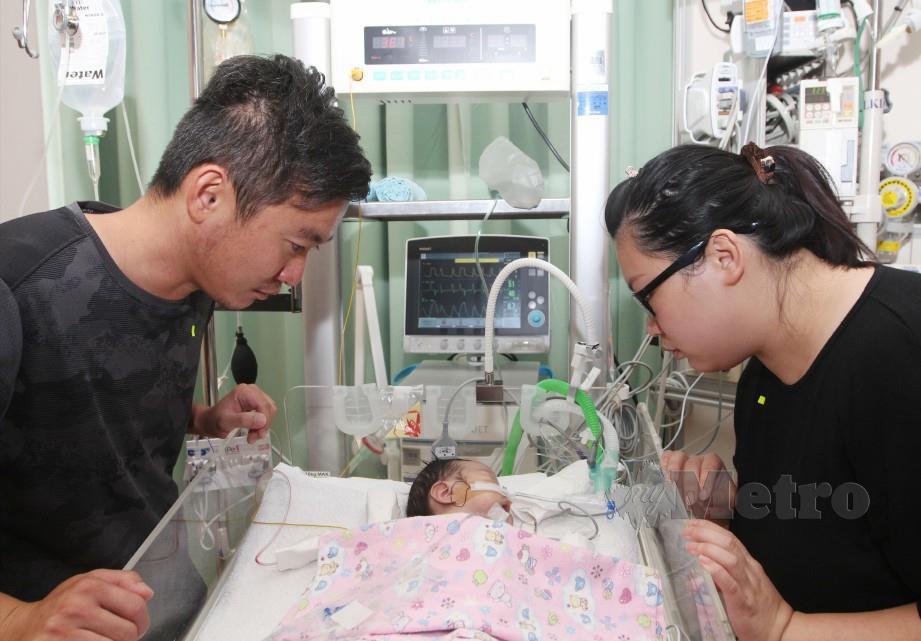 YONG Chai (kiri) dan Suet Man bersama anak mereka yang mengalami penyakit jantung berlubang kini dirawat di Gleneagles Kuala Lumpur. FOTO MUSTAFFA KAMAL