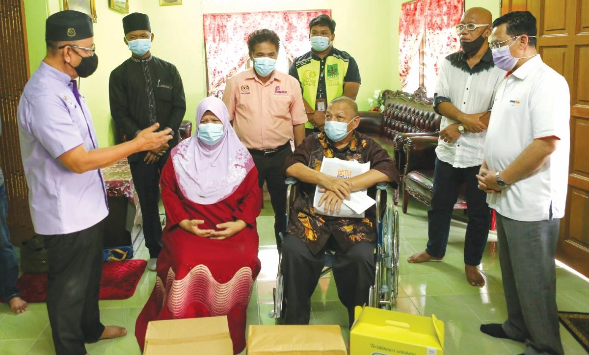 ZAKARIA (kiri) ketika berkunjung menziarahi  waris Allahyarham Tan Sri P Ramlee, Sazali dan isterinya, Hamidah Hitam di kediaman pasangan itu di Semenyih, Selangor.