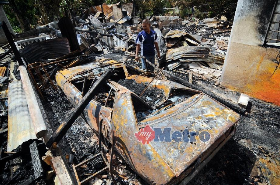 ROSLAN melihat kereta arwah bapanya yang musnah dalam kebakaran rumah emaknya di Felda Sungai Retang, Jerantut, malam tadi. FOTO Nazirul Roselan