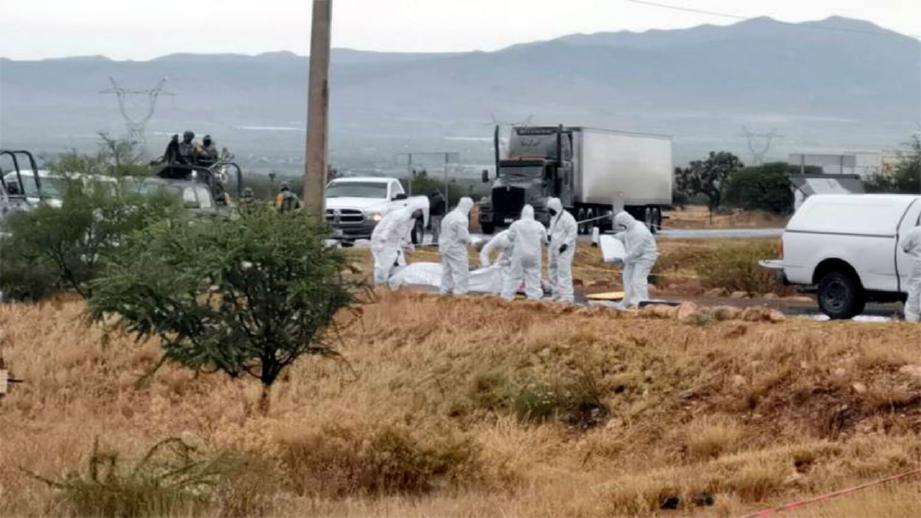 PASUKAN forensik mengakat mayat yang ditemui. FOTO AGENSI