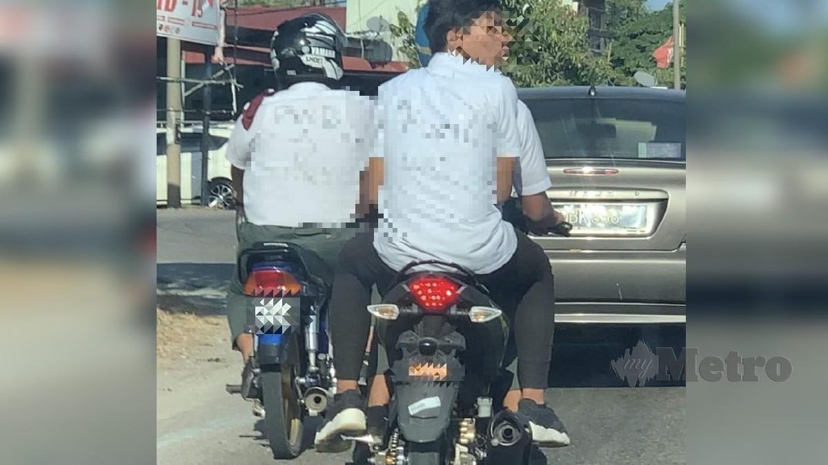 DUA pelajar membonceng motosikal dengan baju diconteng perkataan mencarut dan menghina guru. FOTO ihsan pembaca