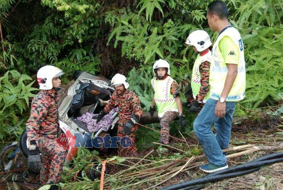 ANGGOTA bomba dan polis mengeluarkan mangsa yang tersepit di dalam kereta yang terbabas ke dalam gaung di Kilometer 12, Jalan Pasir Raja dekat Kuala Jengai, Dungun, hari ini. FOTO Rosli Ilham.
