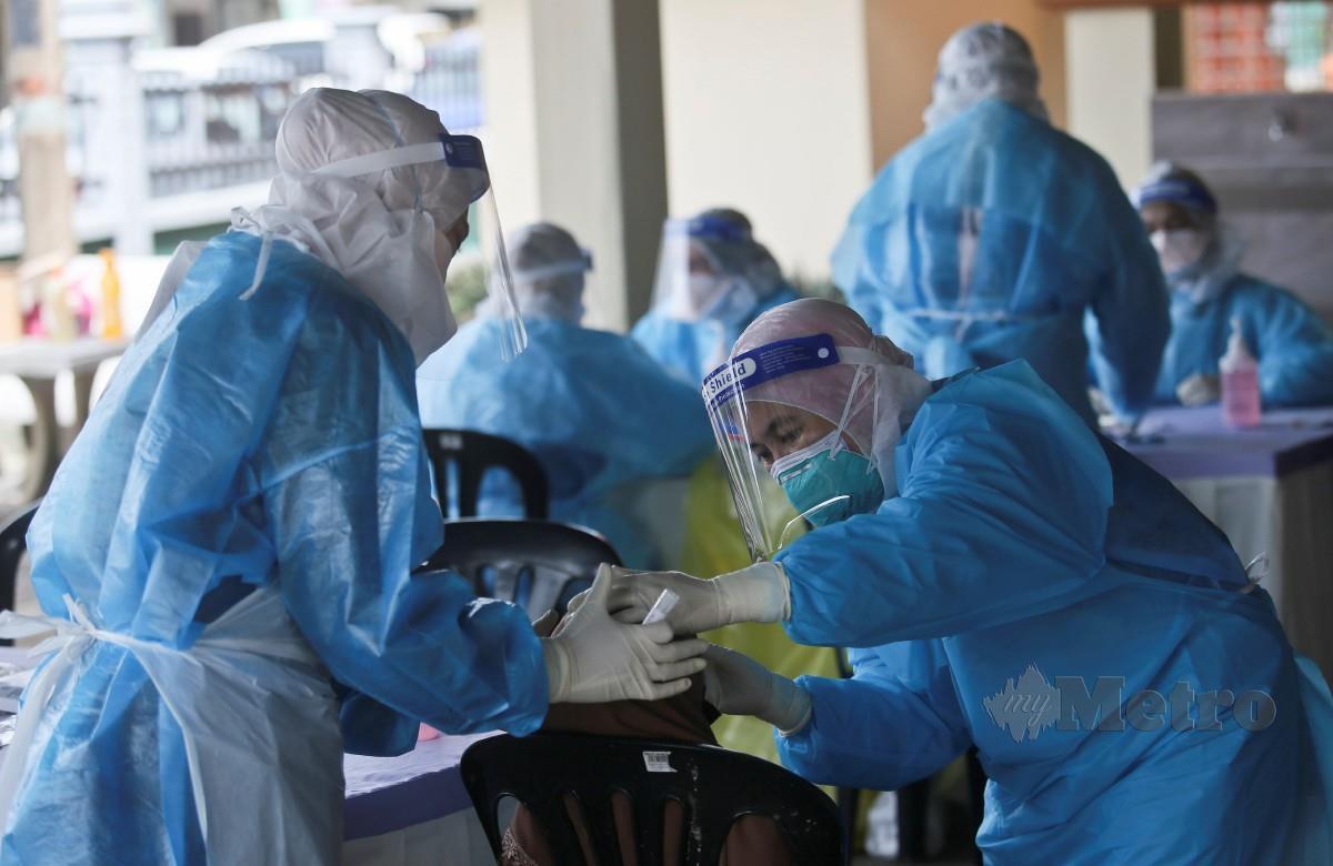 PETUGAS Jabatan Kesihatan melakukan ujian saringan Covid-19 terhadap penduduk di Kampung Teluk Menara, Manir, Terengganu. FOTO Ghazali Kori.