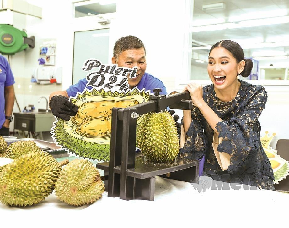 SISSY (kanan) cuba mengupas  buah durian.