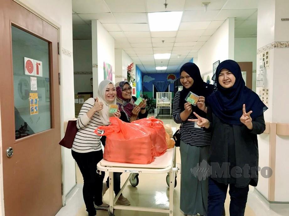 DR Anis (kanan) bersama rakan lain menjayakan program agihan makanan kepada penjaga pesakit dan kakitangan hospital.