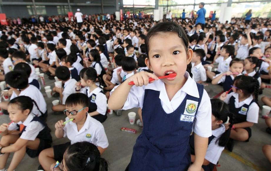 MURID sekolah memberus gigi beramai-ramai dalam usaha cipta rekod.