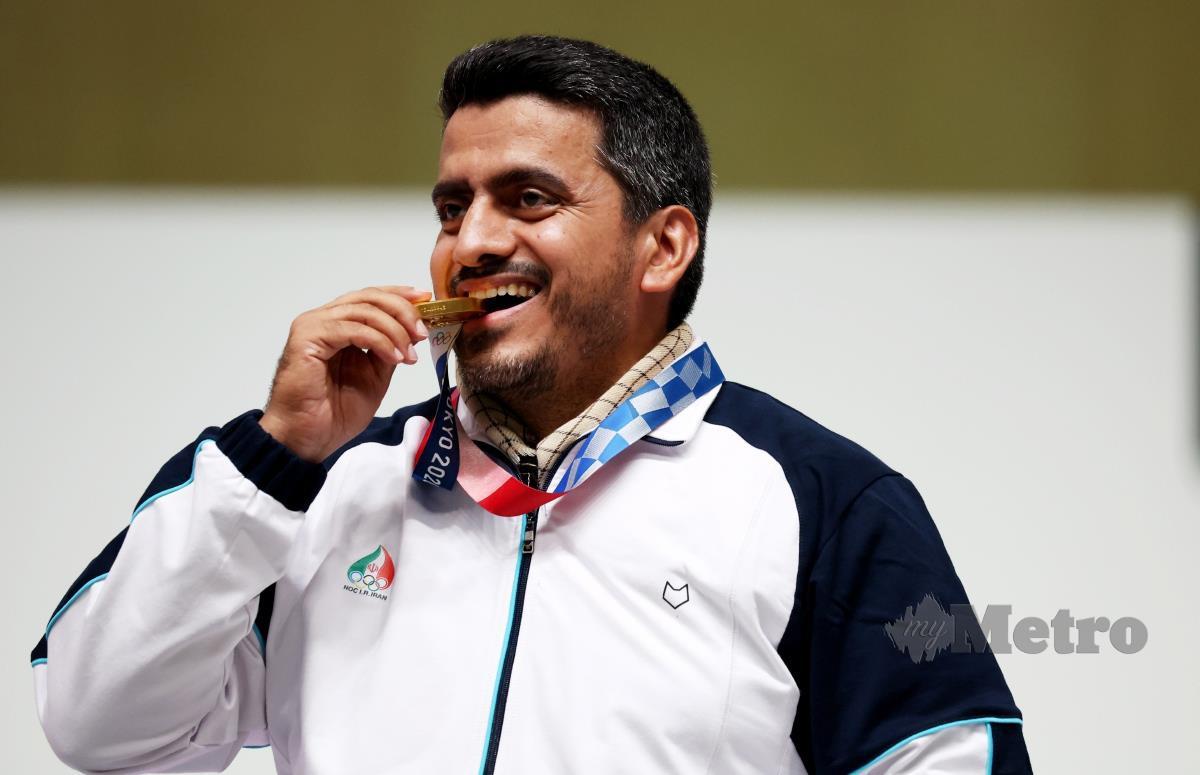 PENEMBAK Iran, Javad Foroughi mengigit pingat emas selepas memenangi acara final 10 meter Air Pistol lelaki semalam. FOTO EPA