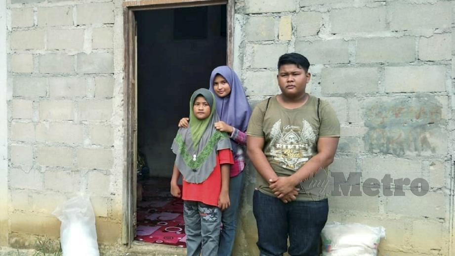 MOHAMAD Syahadam bersama dua adik perempuannya di depan rumah mereka. FOTO Ramli Ibrahim.