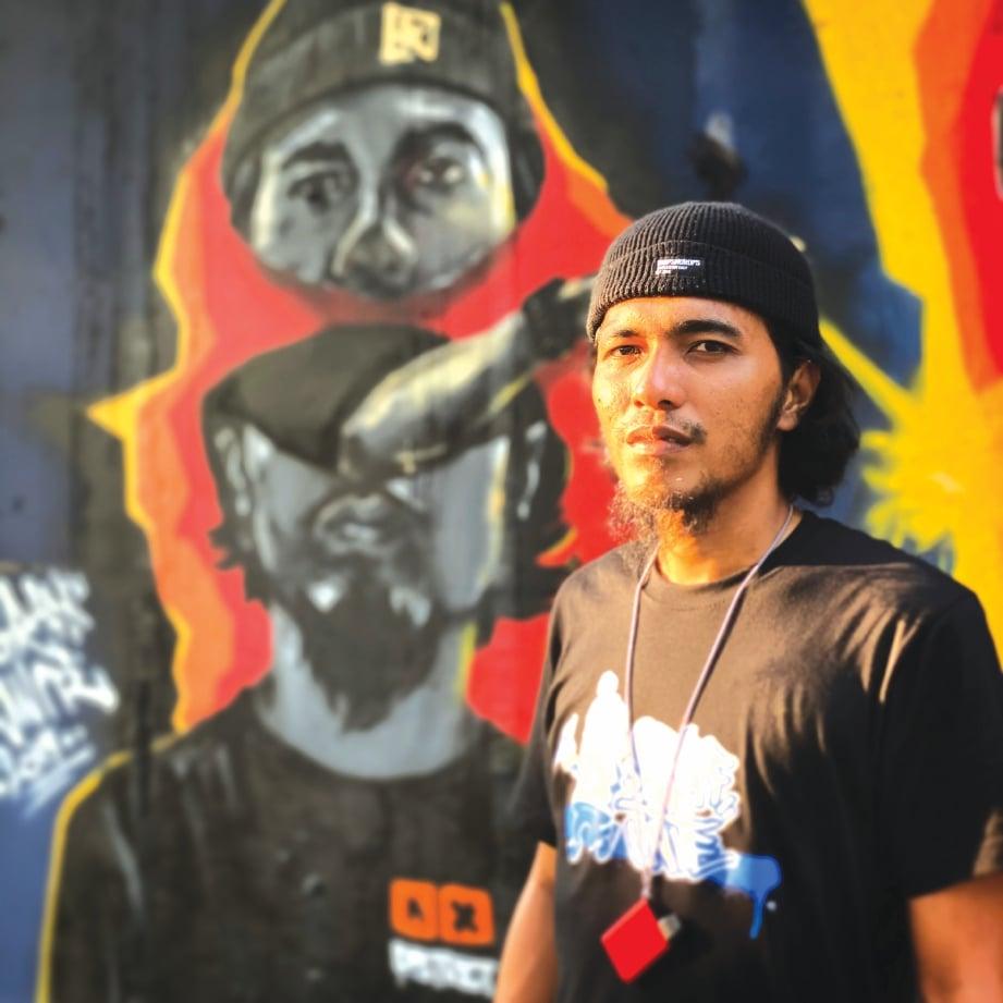 MUHAMMAD Afiq bersama karya seni jalanan yang memaparkan potretnya sendiri. FOTO Ihsan Muhammad Afiq Othman