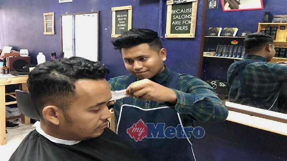 MOHAMAD Hafiz menggunting rambut pelanggan di Bampishh Barbershop di USM Pulau Pinang.