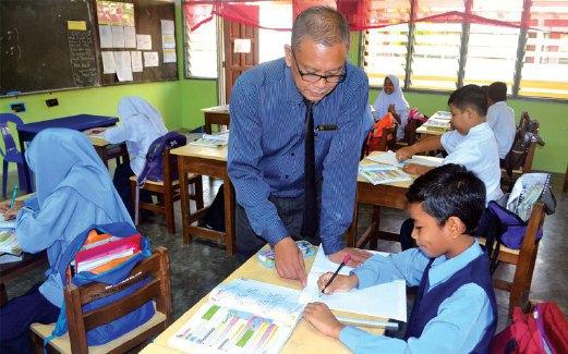 MOHD Kosnan menunjuk ajar seorang pelajarnya sewaktu sesi pembelajaran.
