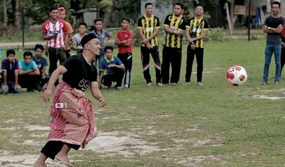 CHE AM berkain sarung ketika bermain bola.