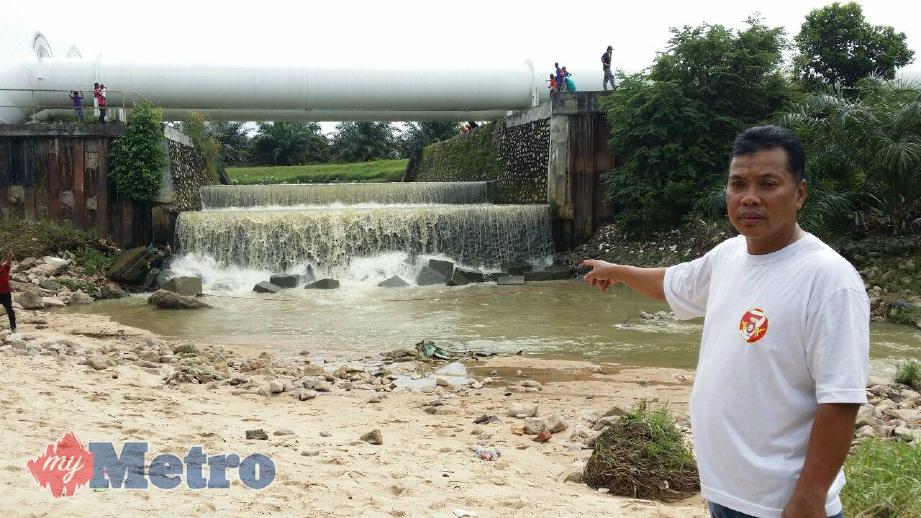 Anuar menunjukkan lokasi Muhammad Fareezuan dihanyutkan arus deras di Sungai Plentong. FOTO Izlaily Nurul Ain Hussein