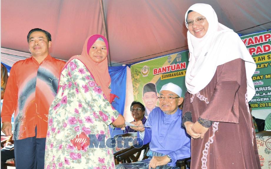 Harussani (dua kanan) menyampaikan bantuan kepada salah seorang penerima di majlis penyampaian bantuan Aidilfitri kepada fakir miskin. FOTO Shaiful Shahrin Ahmad Pauzi