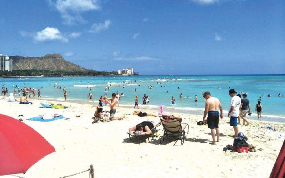 PANTAI Waikiki sentiasa penuh dengan pengunjung dan orang ramai boleh melihat bukit Diamond Head dengan jelas.