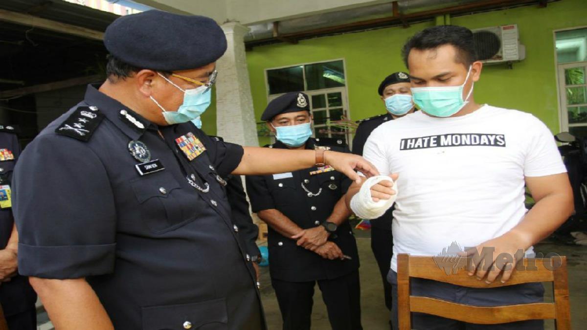 Shafein melihat kecederaan dialami Tuan Hafizuddin ketika melawatnya di Kampung Perupok, Bachok hari ini. Foto Nik Abdullah Nik Omar