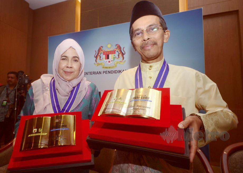 ASARIAH dan Nawi bersama anugerah yang diterima. -Foto SHAHNAZ FAZLIE SHAHRIZAL