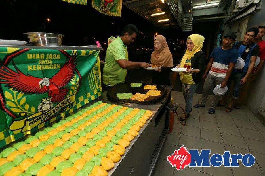 Mohd Najmuddin (kiri) menghidangkan roti canai Hijau Kuning secara percuma sebanyak 600 keping kepada pelanggan tanda sokongan kepada penonton sebagai hadiah pasukan Kedah layak ke perlawanan akhir Piala Malaysia menentang JDT pada 4 November ini di Stadium Shah Alam. FOTO SHAHRIZAL MD NOOR