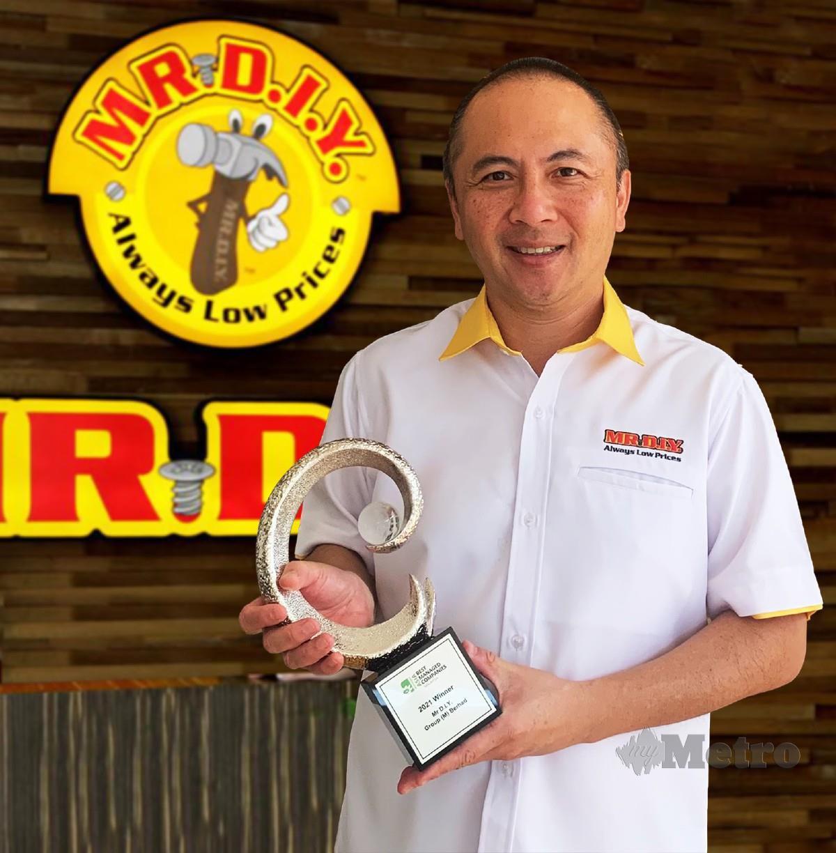 ADRIAN bersama anugerah yang dimenangi MR DIY.