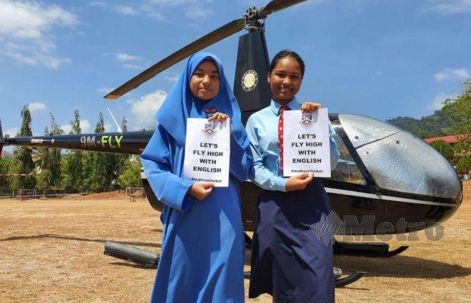 PELAJAR, Myra Anne (kanan) dan Laila Maisara Nazrat ceria bersama kertas yang bertulis 'Let's Fly High With English' sebelum menaiki helikopter sebagai gimik perasmian Program Imersif Tinggi di Langkawi. FOTO Hamzah Osman