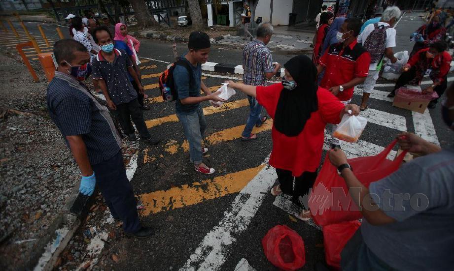 PERTUBUHAN Kebajikan Ehsan Penyayang, tampil menghulurkan bantuan makanan dan penutup mulut dan hidung kepada gelandangan yang masih bertebaran di bandar raya ini. FOTO Mohd Azren Jamaludin