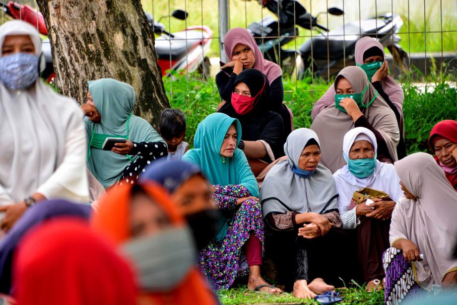 SEBAHAGIAN wanita menanti pengedaran makanan berbuka walaupun berdepan ancaman Covid-19 di Blang Bintang, Aceh. - AFP