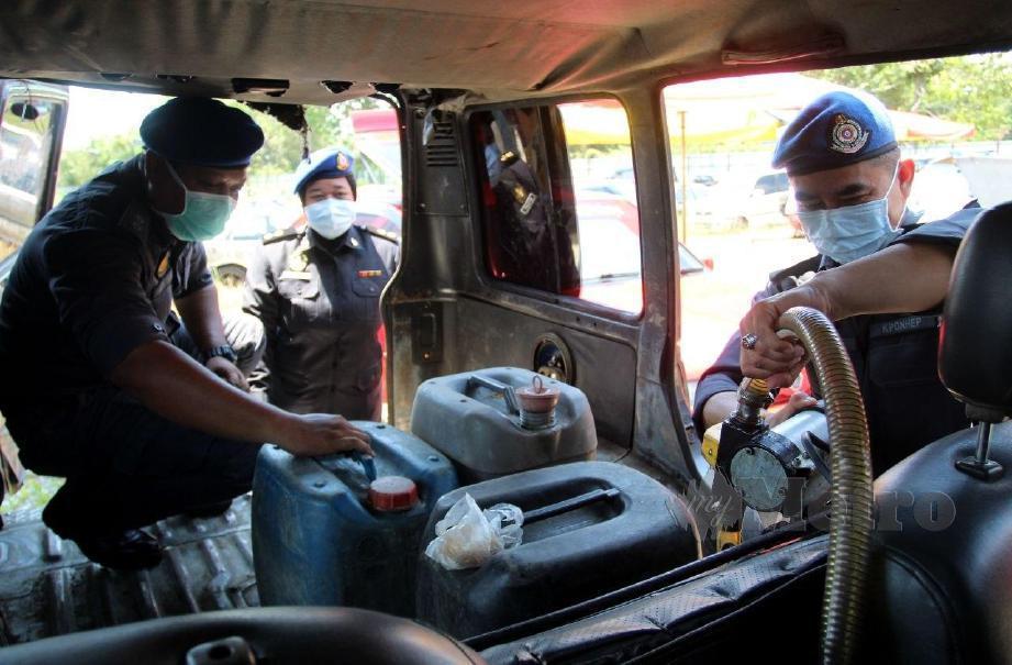 KPDNHEP Kelantan memeriksa meriksa wayar pam minyam serta tong plastik berisi minyak patrol di dalam kereta yang dipercayai untuk diseludup ke negara jiran. FOTO Nik Abdullah Nik Omar
