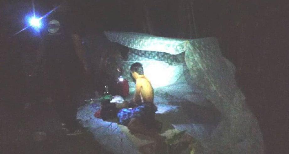 ANGGOTA  AADK Besut memeriksa lelaki yang ditemui tinggal dalam kelambu belakang rumah dalam Operasi Cegah di Kampung Kerandang kira-kira jam 5.45 pagi semalam-Insan AADK Besut.