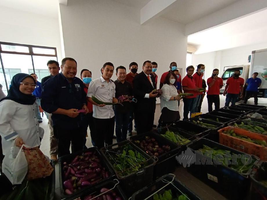 MOHD Hafiz (tiga dari kiri) dan Datuk Sawalludin melihat hasil tani yang diterima oleh PPK Kluang di Pusat Pengumpulan Hasil Pertanian pertubuhan itu. FOTO Adnan Ibrahim