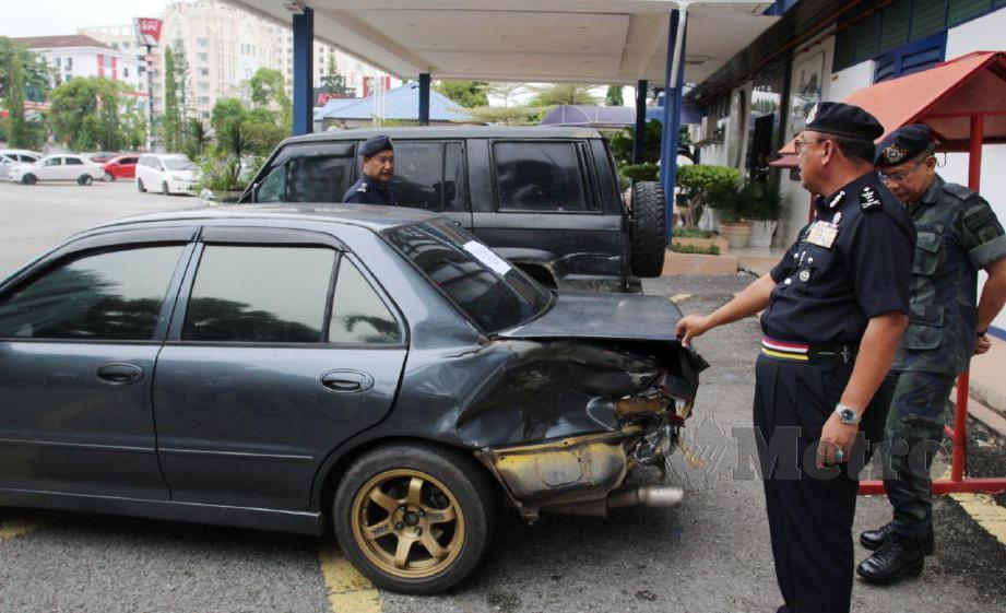 SHAFEIN Mamat (kiri) menunjukkan kesan rempuhan kereta milik anggota PGA yang dilanggar oleh kereta penyeludup semasa menjalankan tugas. FOTO Nik Abdullah Nik Omar