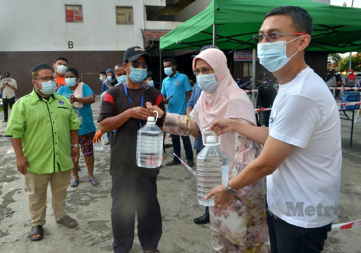 SUHAIMI Kamaralzaman (kanan) dan Rodziah Ismail (dua dari kanan) menyerahkan air minuman kepada penduduk di Rimba Jaya, Shah Alam. FOTO Faiz Anuar