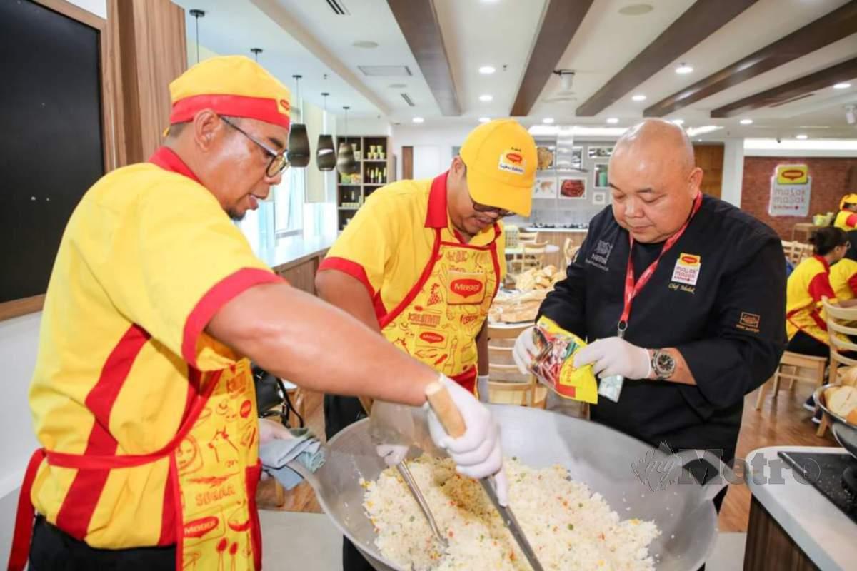 CHEF Muluk (kanan) sedia berkongsi tip bagaimana  menyediakan makanan dalam kuantiti yang banyak.