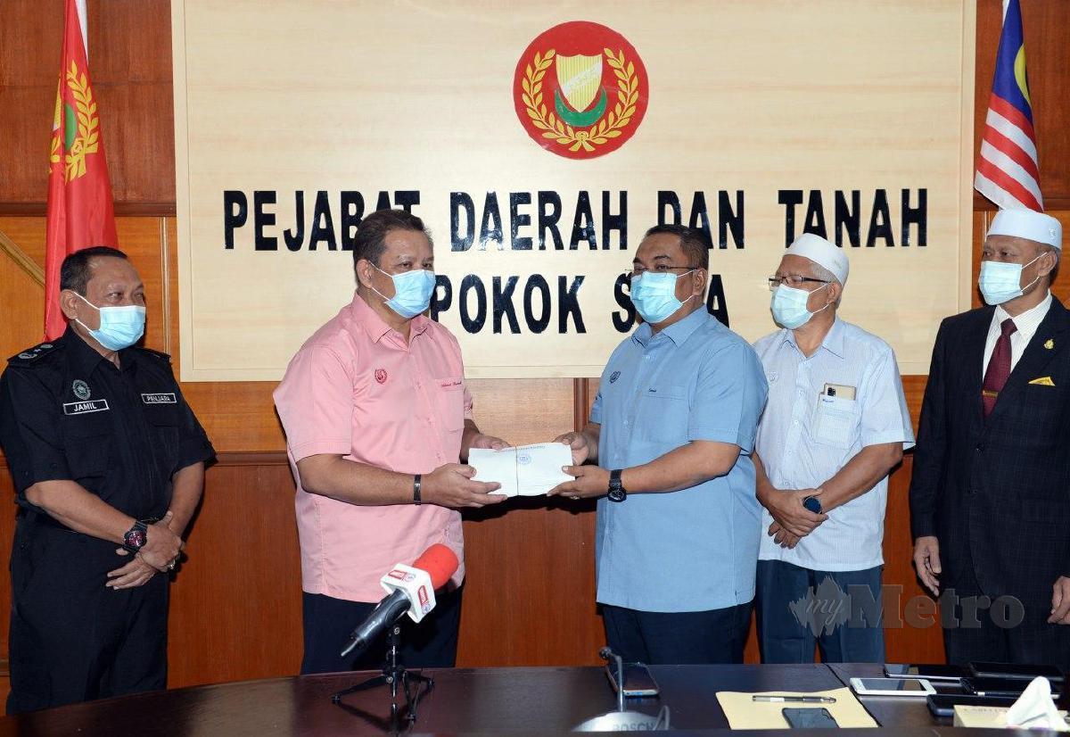 MUHAMMAD Sanusi (tiga dari kanan) menyerahkan sumbangan wang tunai  kepada Ahmad Bawadir  (dua dari kiri) untuk disampaikan kepada  ketua keluarga kakitangan Penjara Pokok Sena. FOTO Amran Hamid