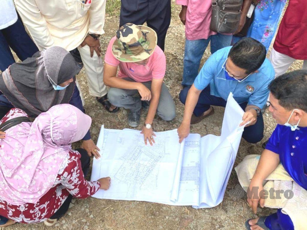 DATUK Jalaluddin Alias (dua dari kanan) melihat pelan projek perumahan SPNB di Simpang Durian ketika mengadakan lawatan ke tapak projek berkenaan.