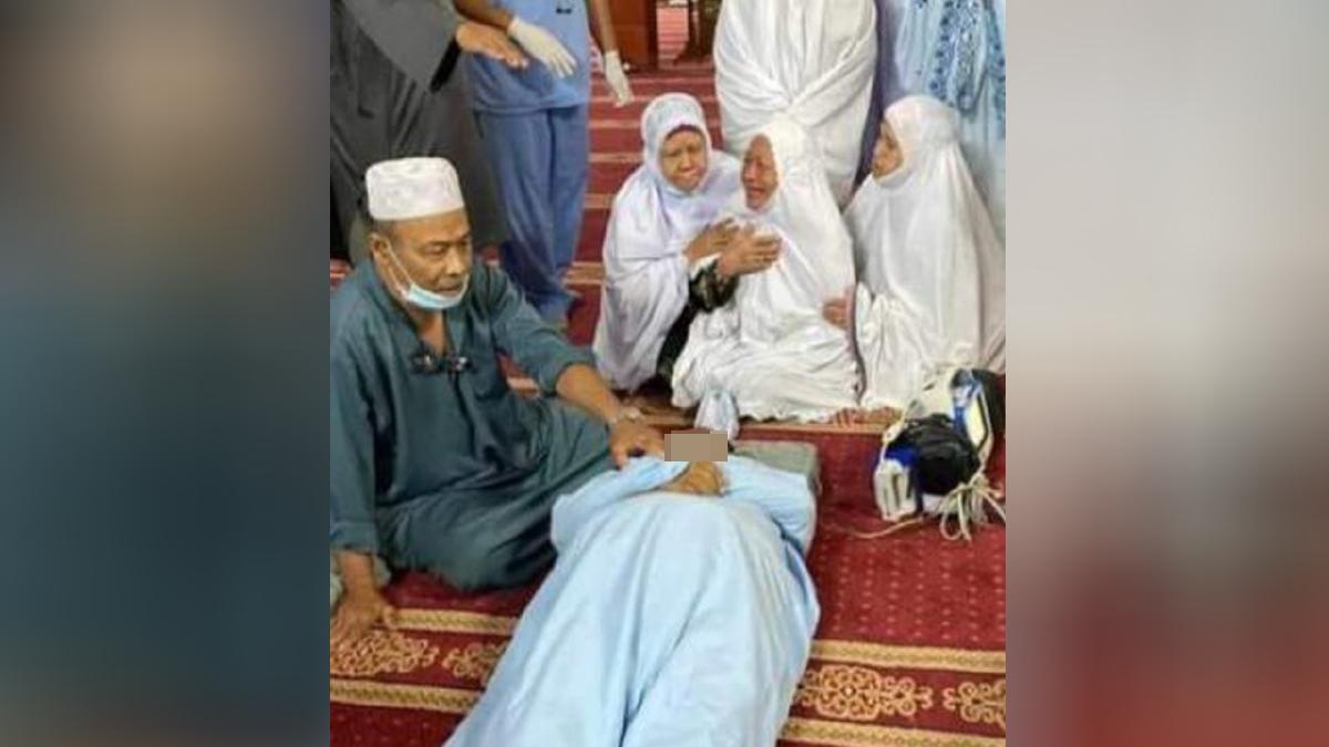 KAPT (B) Harun Othman (Kiri) membetulkan kedudukan jenazah Ibrahim Yasir yang meninggal dunia selepas solat maghrib di Masjid Jamek Al-Yahya, Taman Kluang Barat, Kluang malam tadi. FOTO ihsan PEMBACA